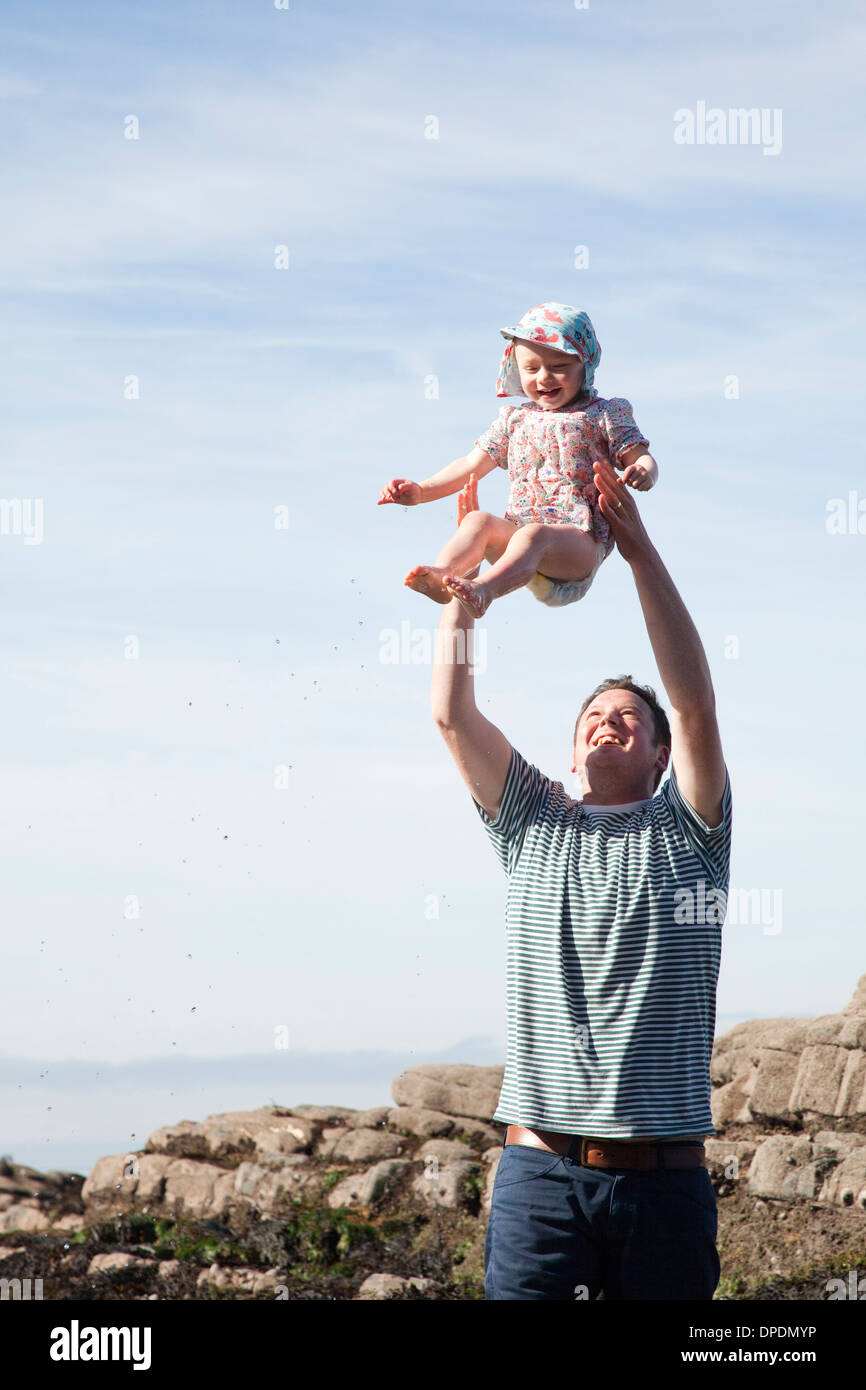 Father throwing child in air on beach - Stock Image