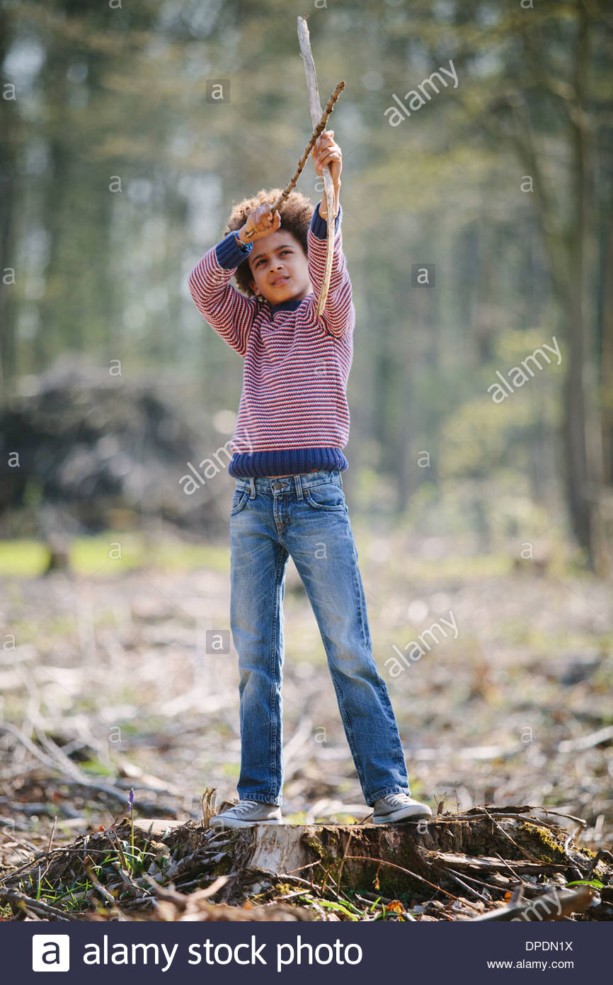 Boy aiming bow and arrow in woods - Stock Image
