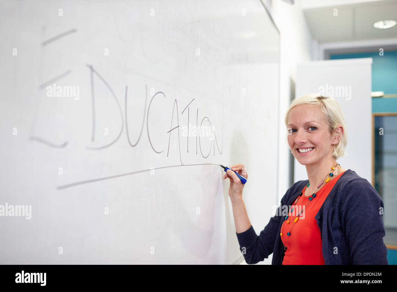 Portrait of female writing on white board - Stock Image