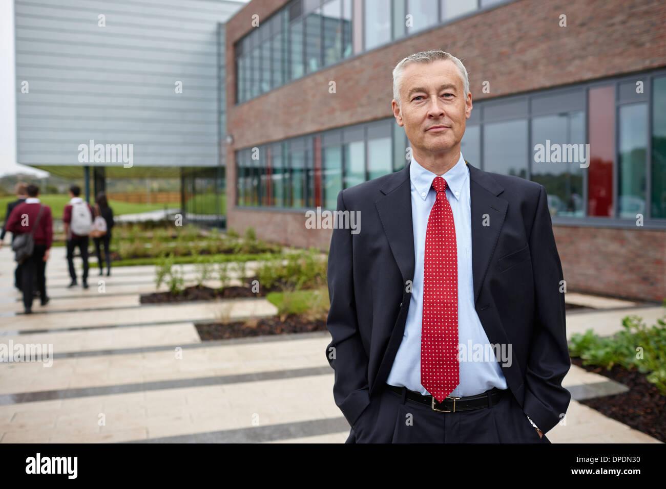 Portrait of mature male teacher outside school - Stock Image