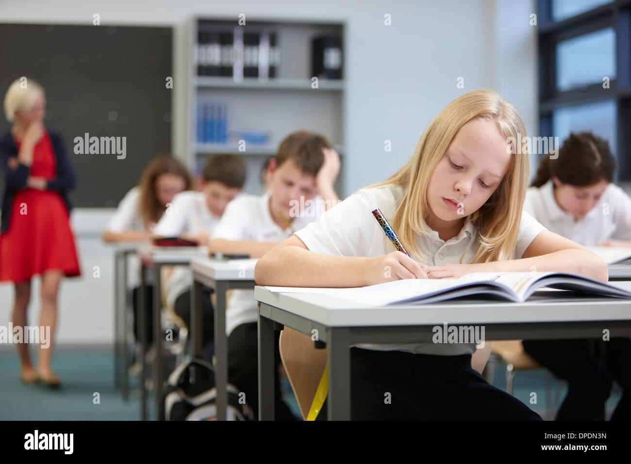 Female teacher watching class doing educational exam - Stock Image