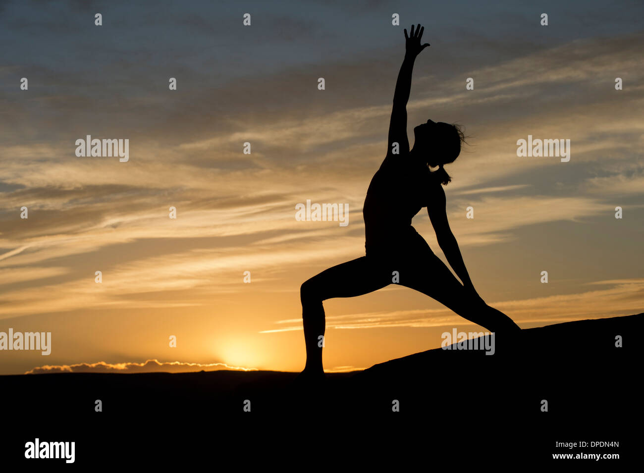 Silhouette of young woman doing yoga, Moab, Utah, USA - Stock Image