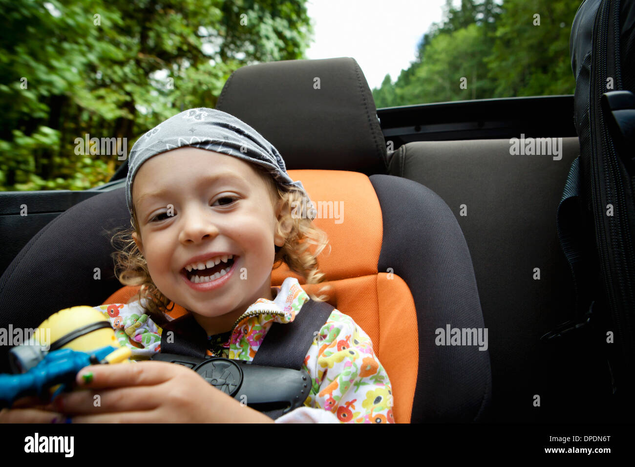 Portrait of female toddler in back seat of open soft top - Stock Image