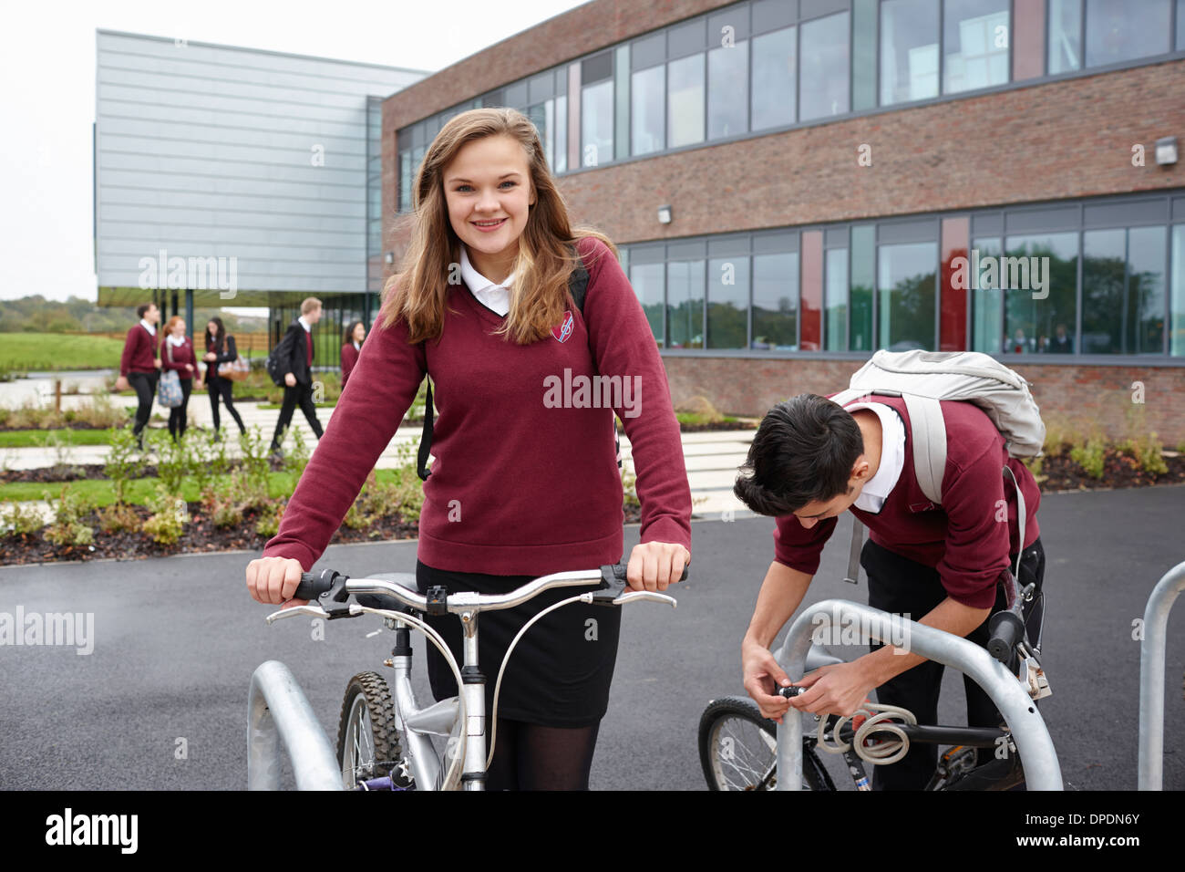 Teenagers unlocking cycles outside school - Stock Image