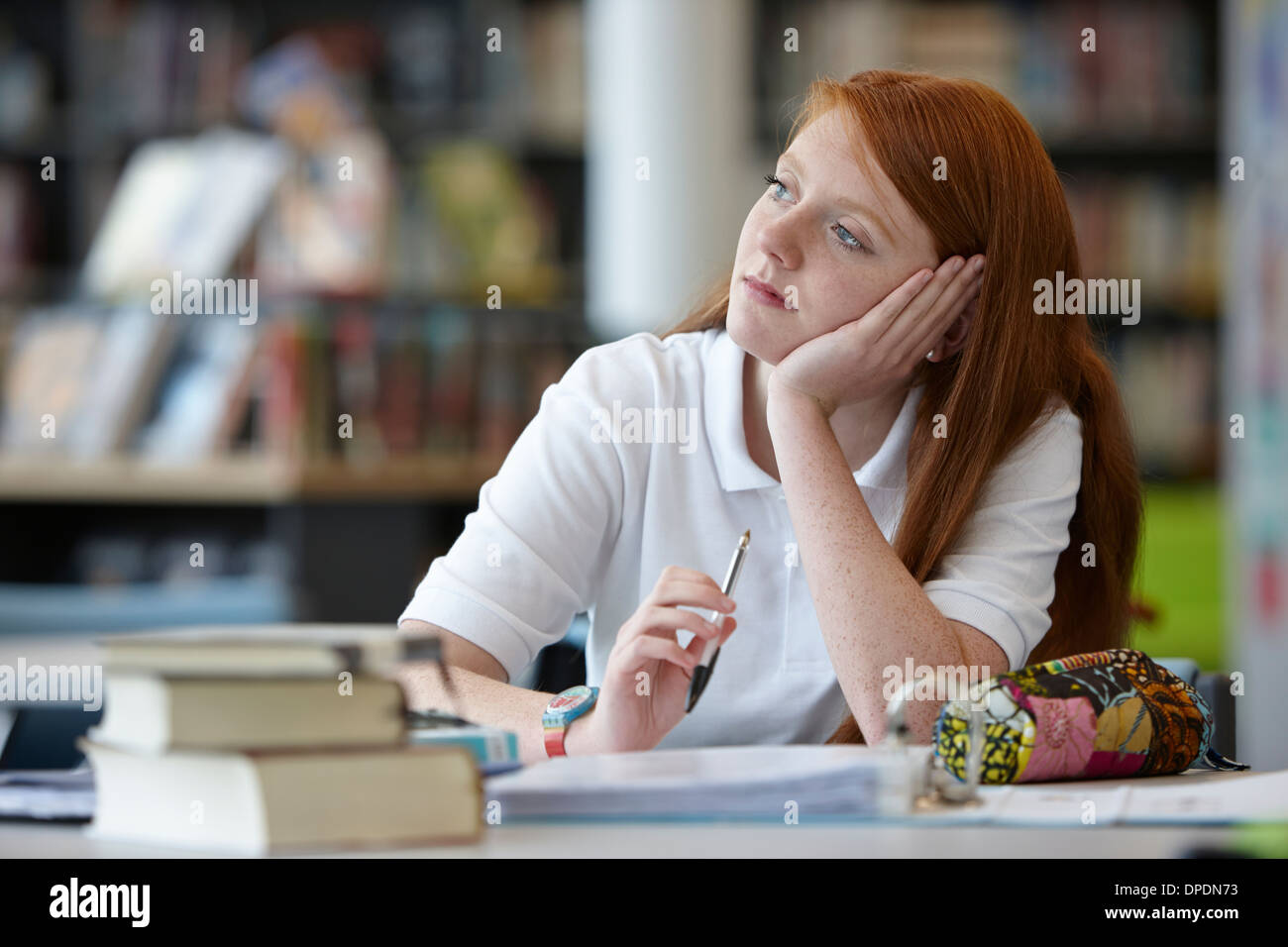 Portrait of teenage girl daydreaming in library - Stock Image