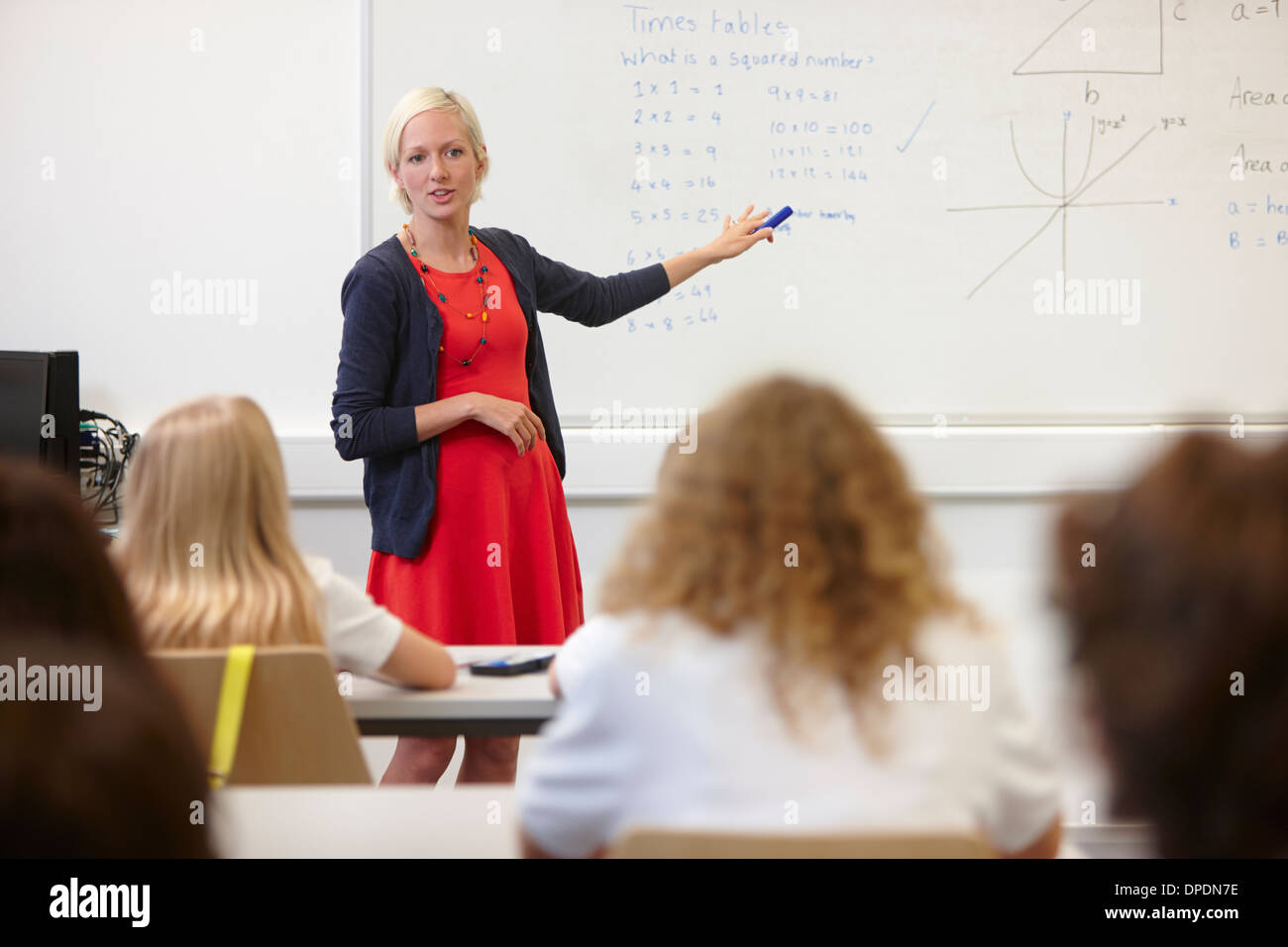 Female teacher using white board in front of class - Stock Image