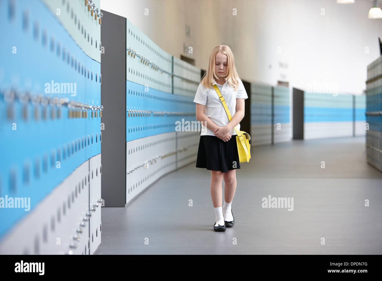 Unhappy schoolgirl walking alone in school corridor - Stock Image