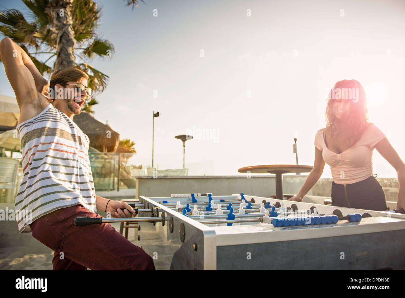 Young couple playing table football at San Diego beach - Stock Image