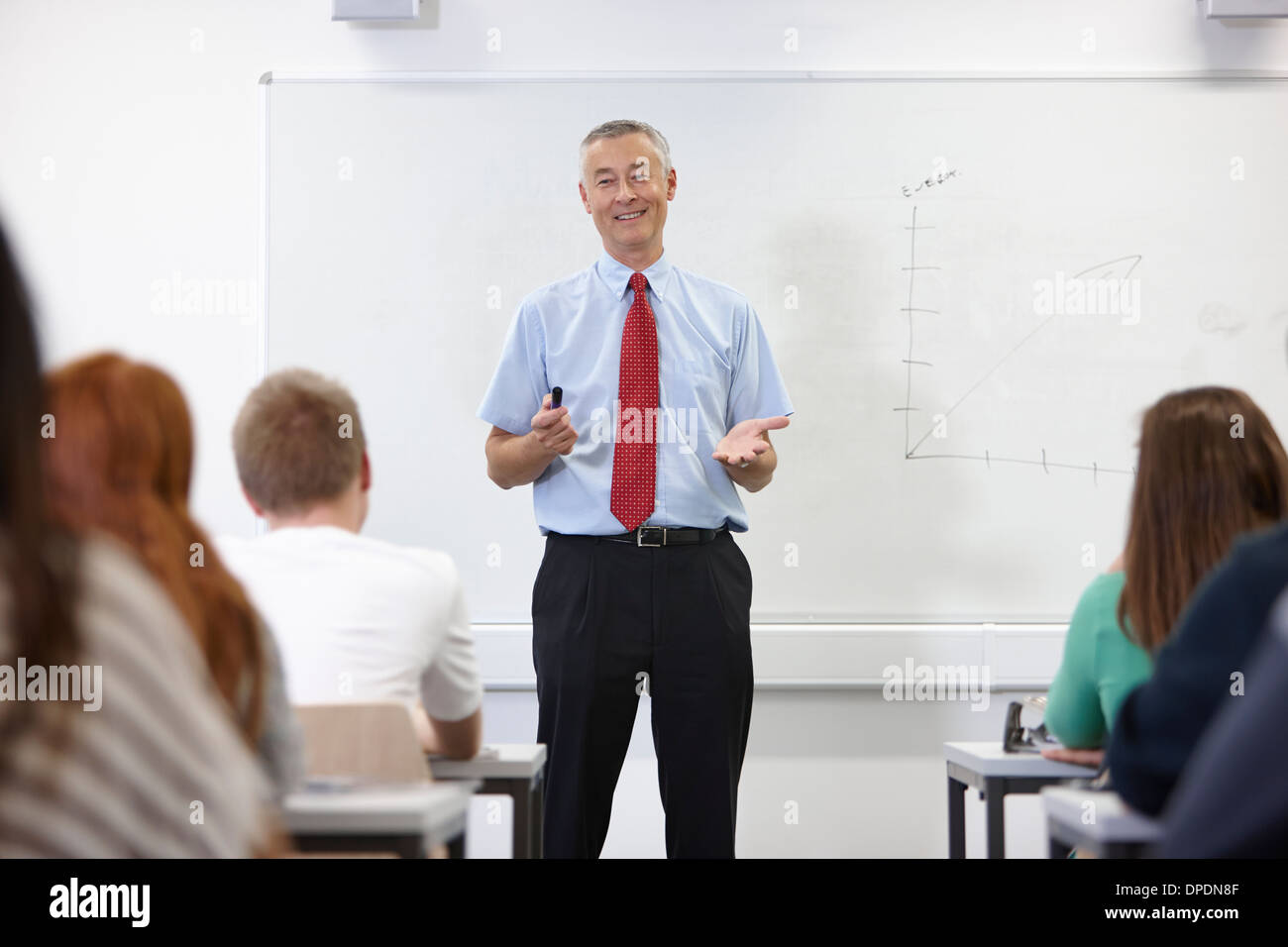 Mature male teacher in front of class - Stock Image