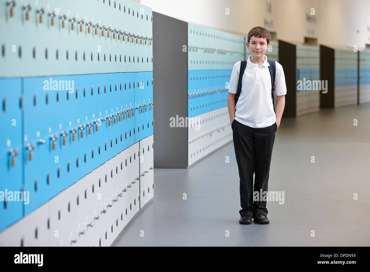 Portrait of schoolboy with hands in pockets in school corridor - Stock Image