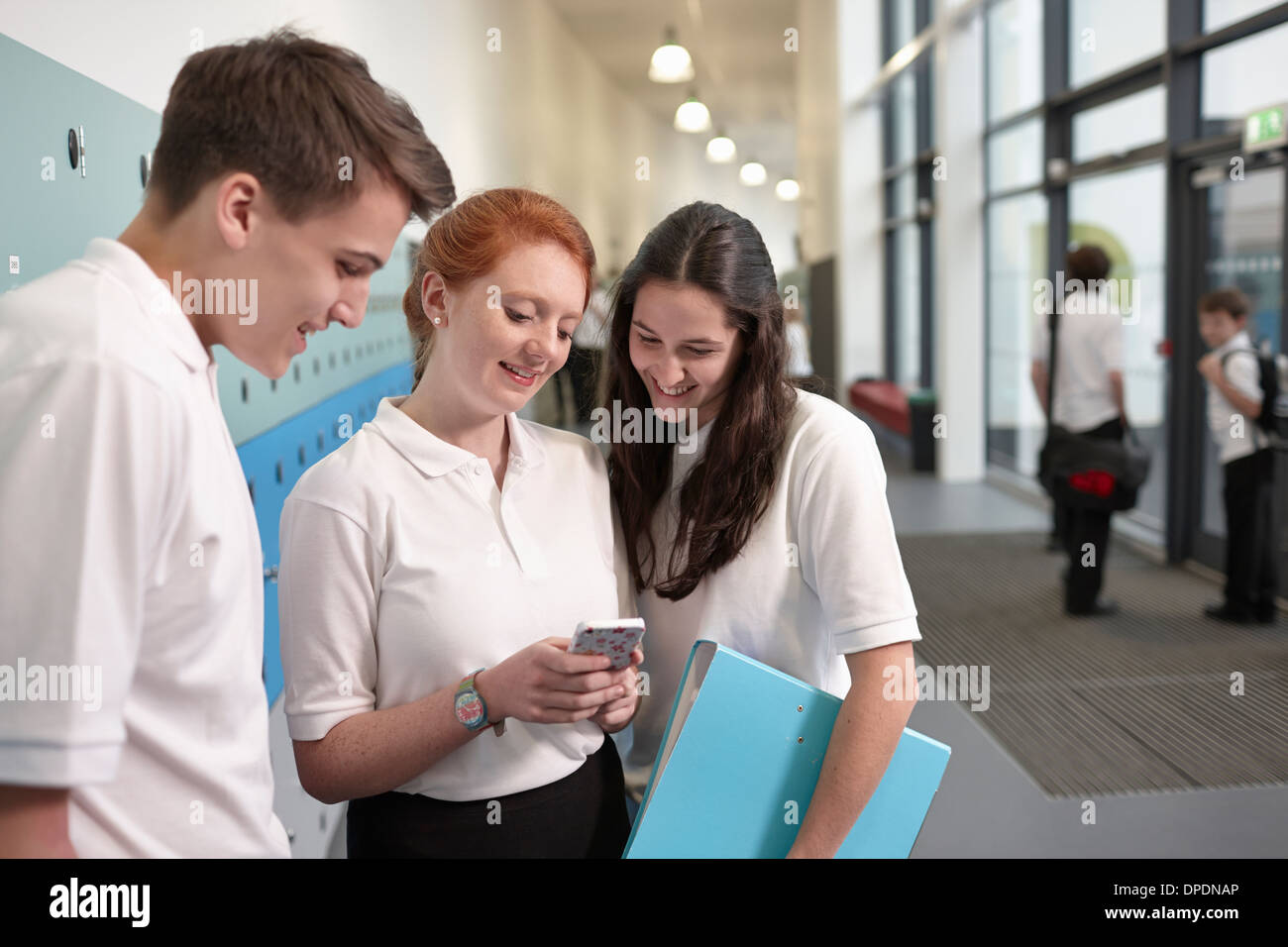 Teenagers looking at mobile phone in school corridor - Stock Image
