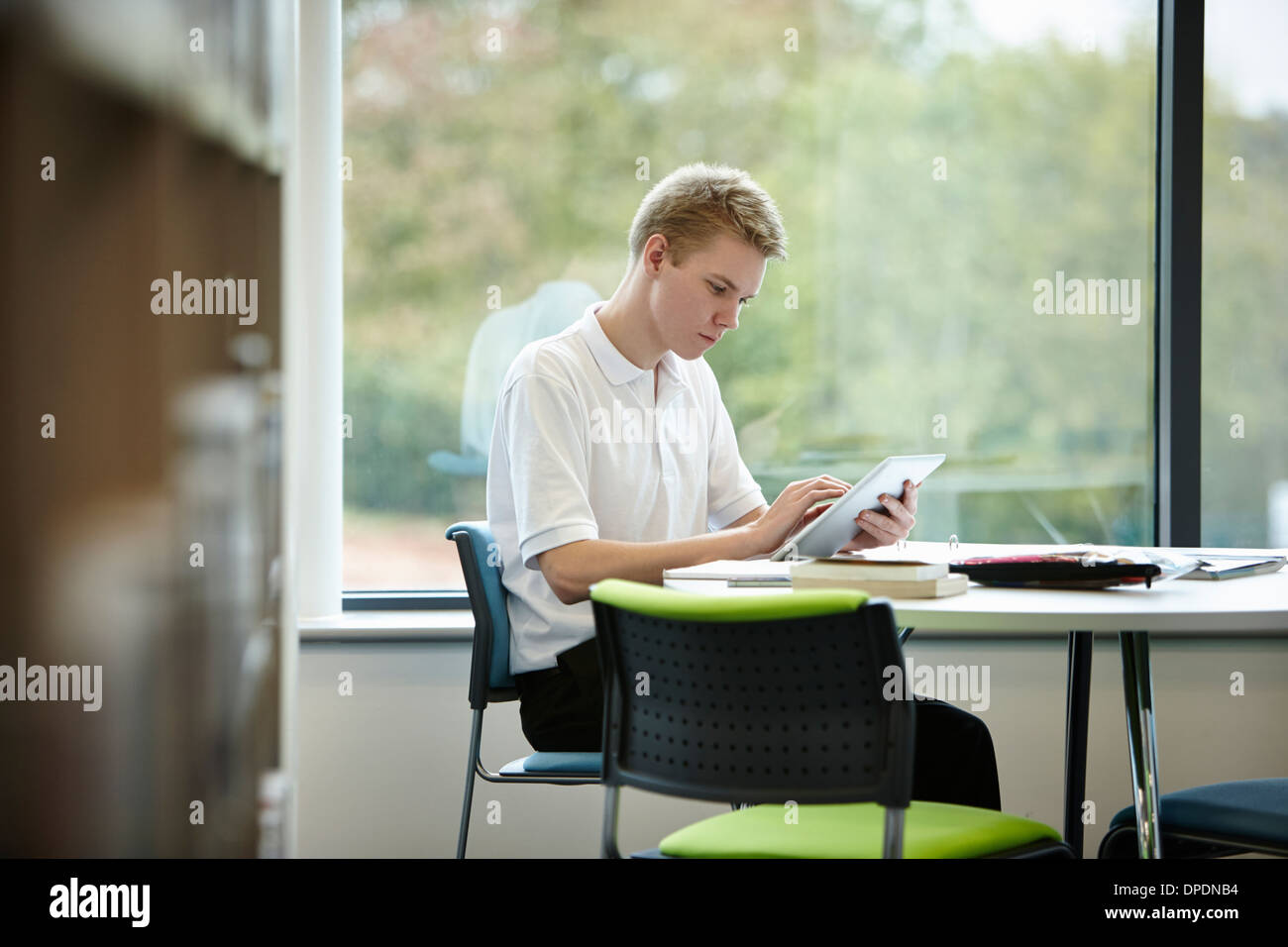 Teenage boy using digital tablet in library - Stock Image