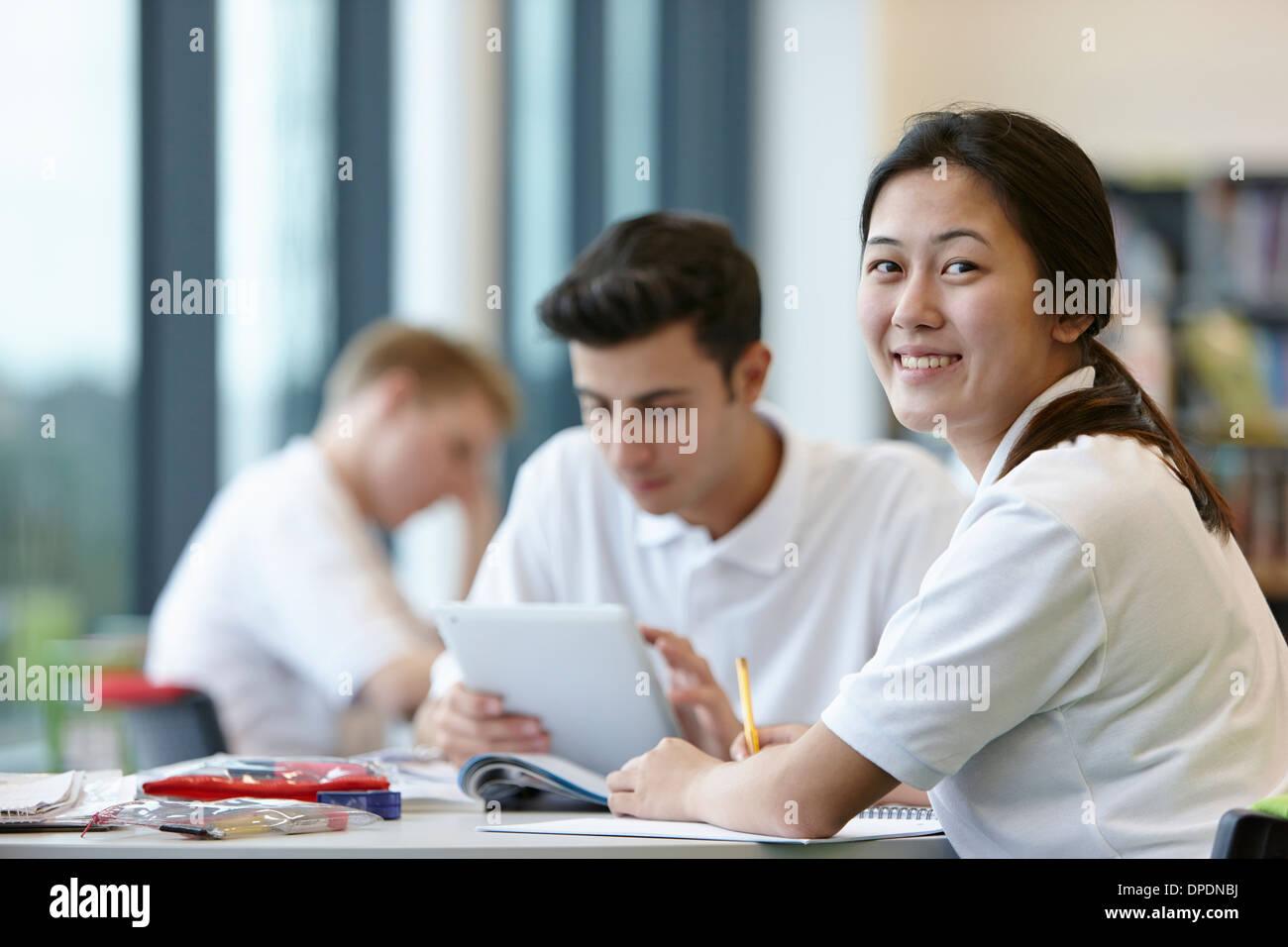 Teenagers working in school classroom Stock Photo