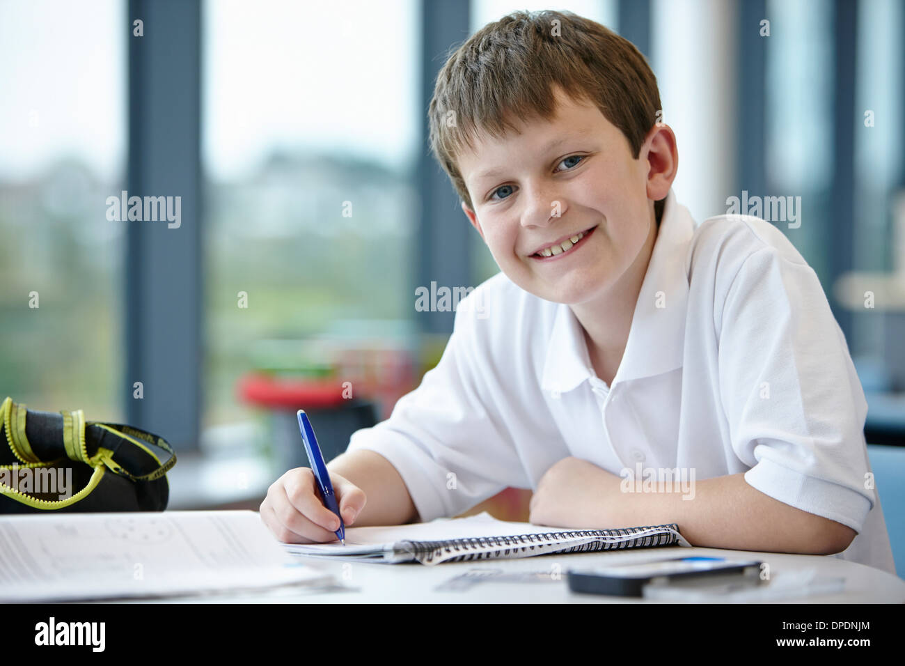 Portrait of schoolboy writing in class - Stock Image
