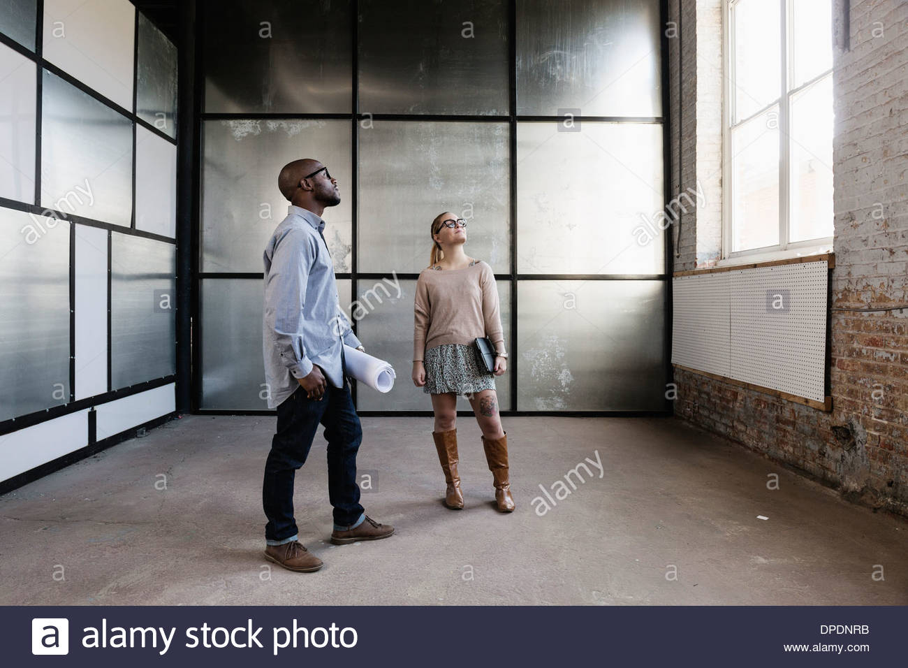 Young business partners looking at new office space - Stock Image