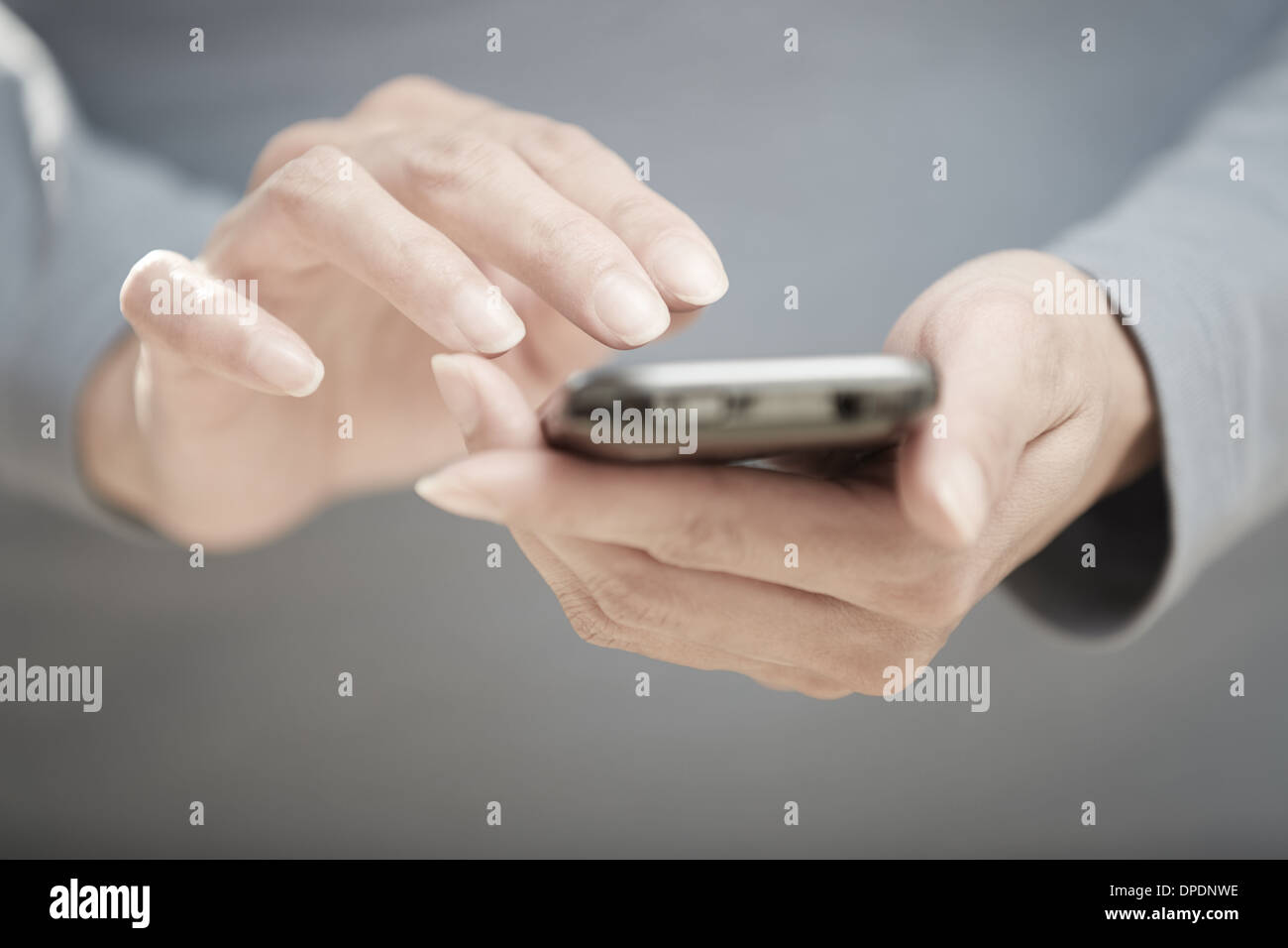 Human hands sending SMS via cell phone - Stock Image