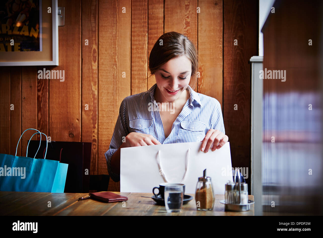 Young woman sitting in cafe looking in shopping bag Stock Photo