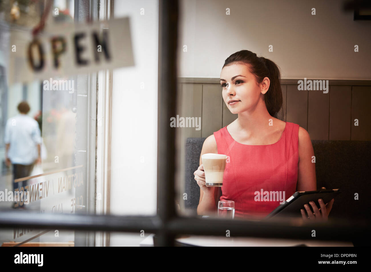 Young woman sitting in cafe with digital tablet and hot drink - Stock Image