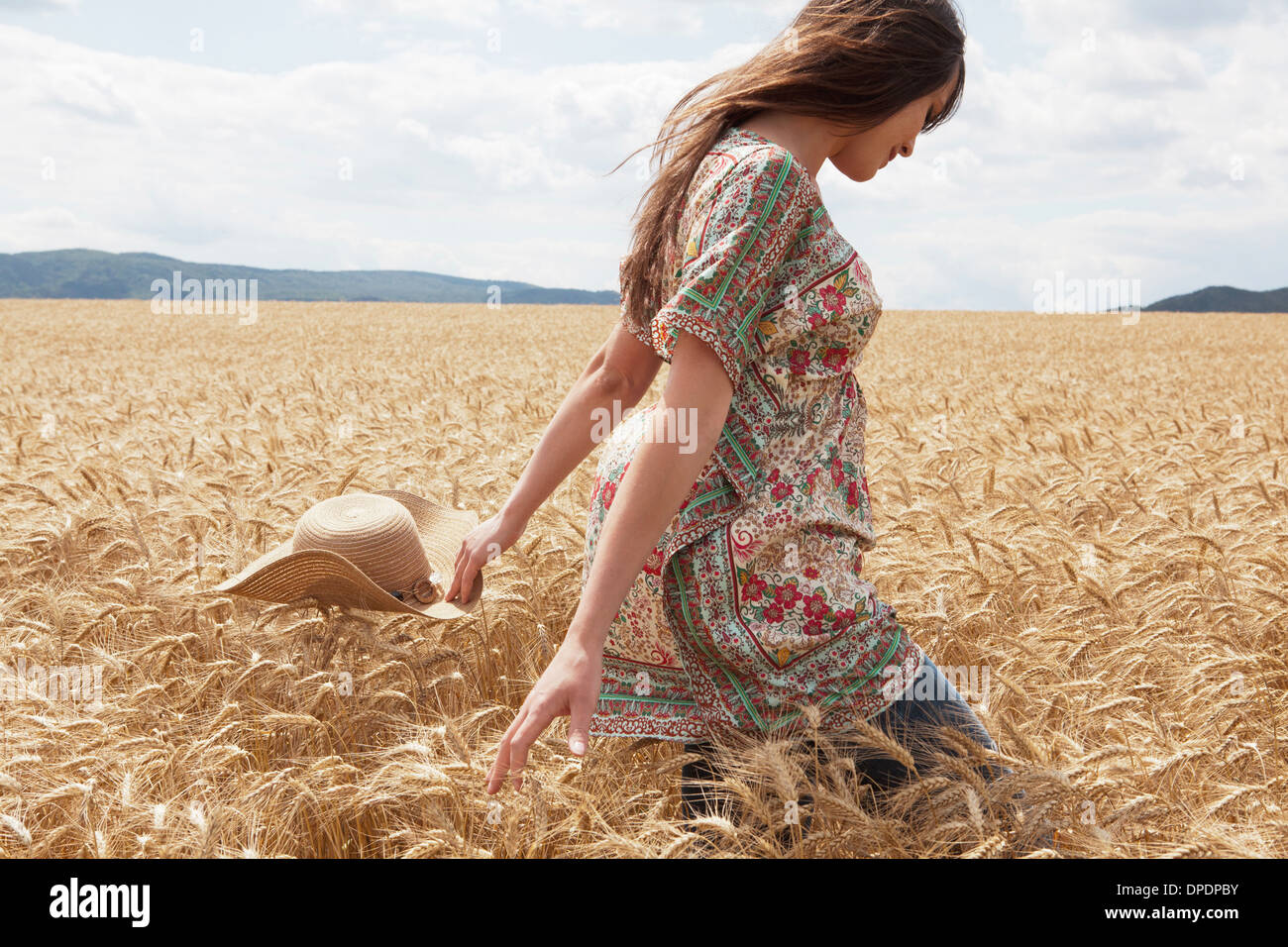 Mid adult woman walking through wheat field - Stock Image