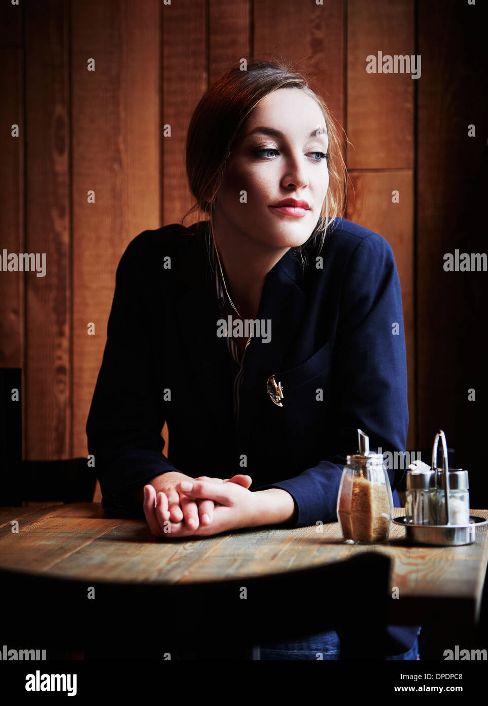 Young woman sitting in cafe with hands clasped - Stock Image