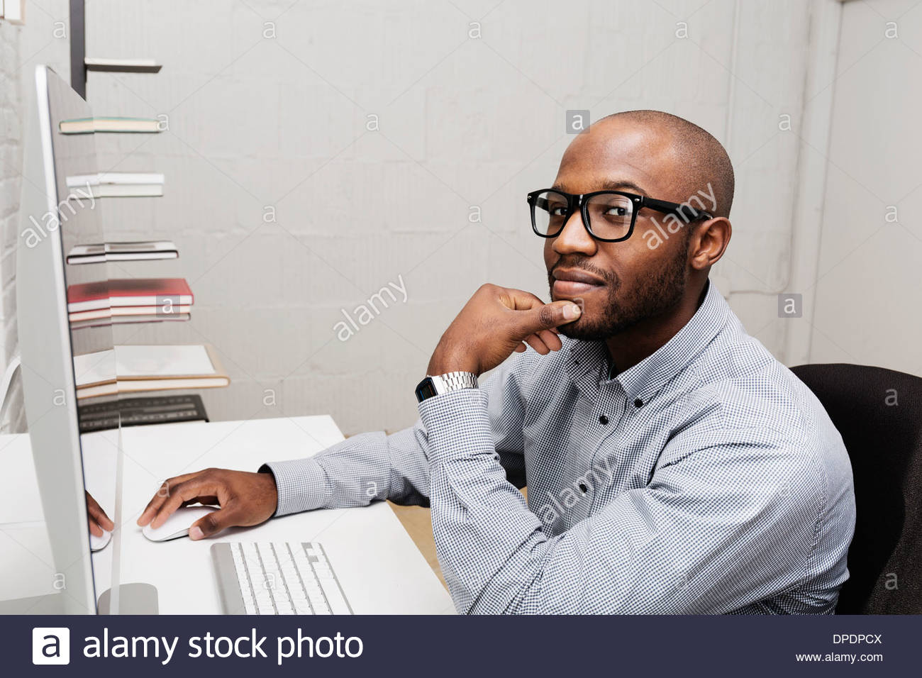 Portrait of young man using computer in design office - Stock Image