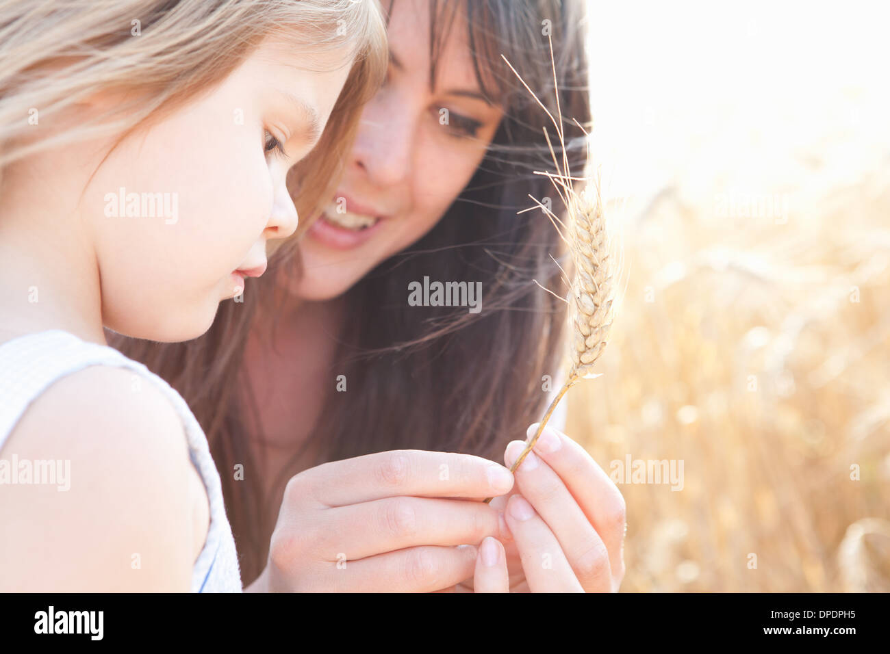 Mother and daughter looking at grain of wheat - Stock Image