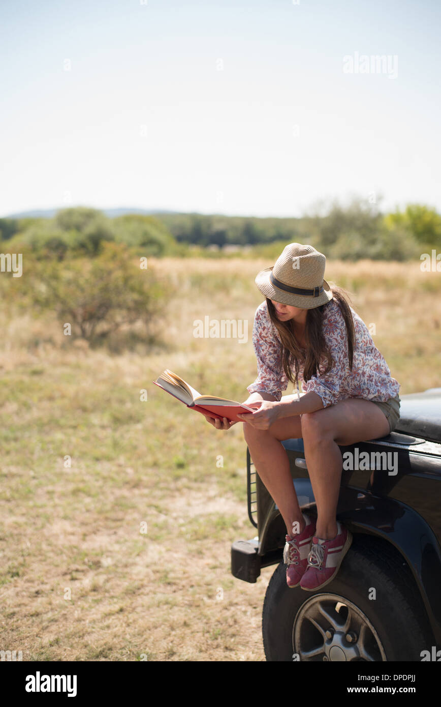 Mid adult women sitting on hood of car reading book - Stock Image