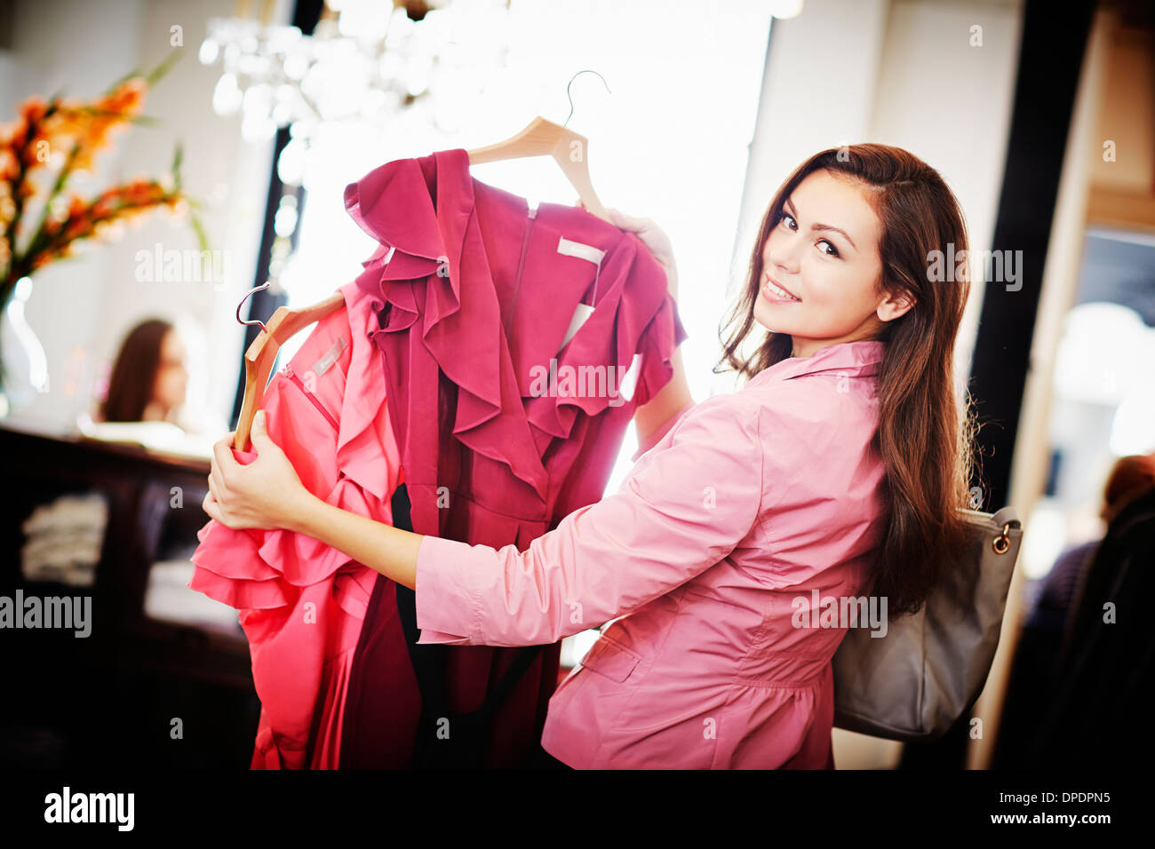 Young woman looking pink top on hanger - Stock Image