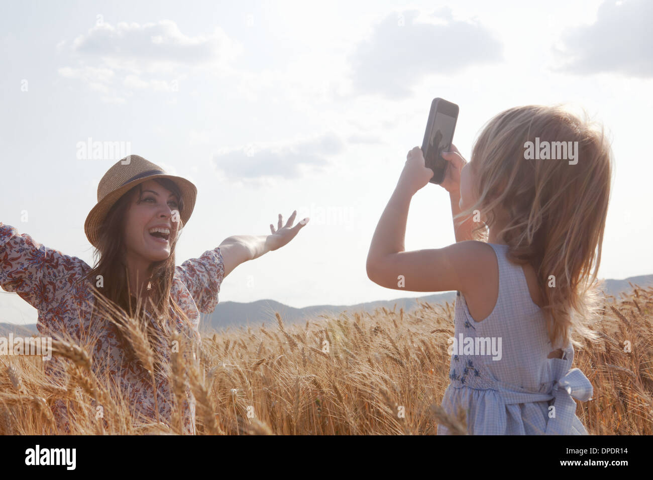 Girl taking photograph of mother in wheat field with arms open - Stock Image