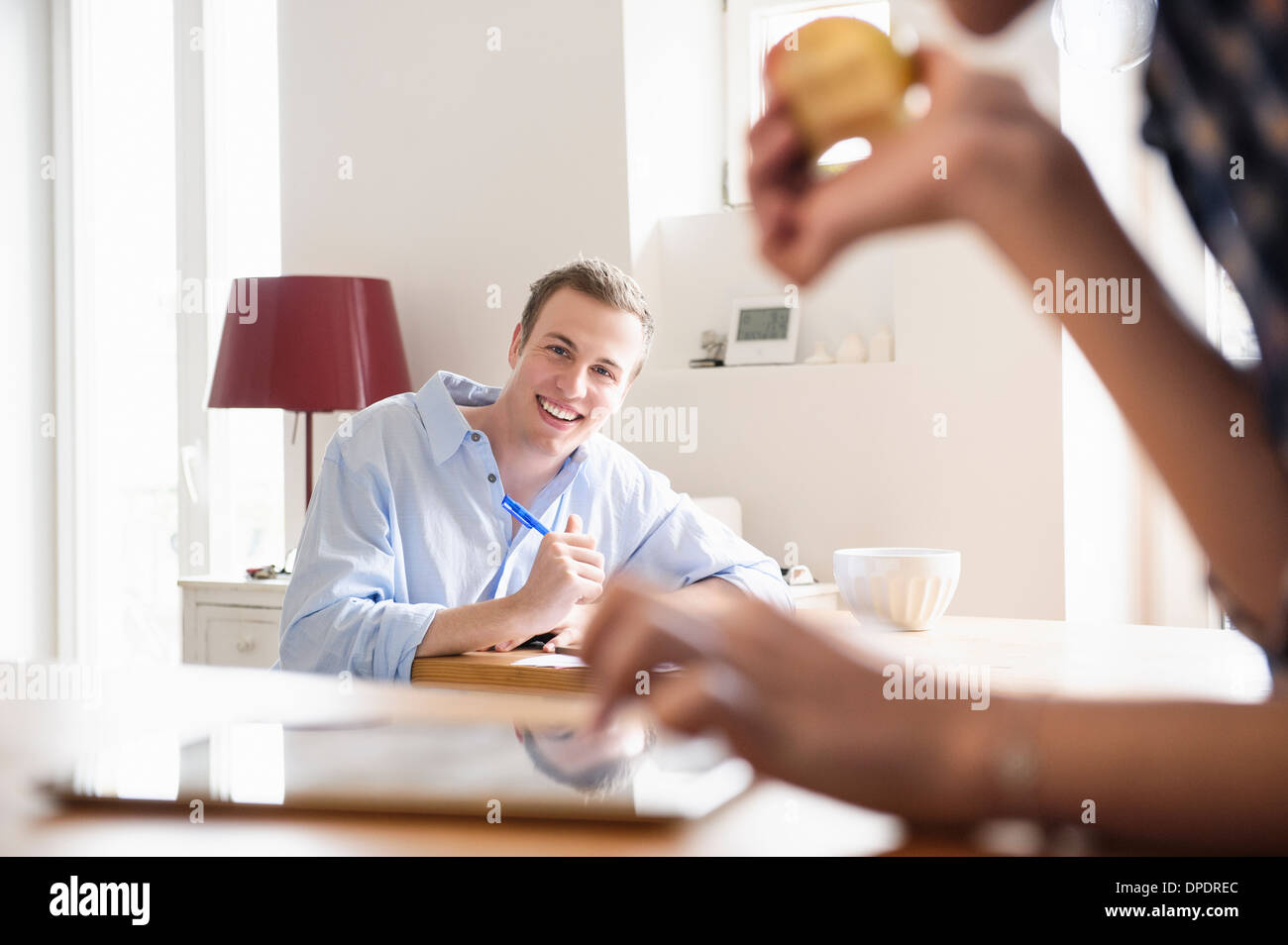 Young man seated smiling at a young woman eating an apple - Stock Image