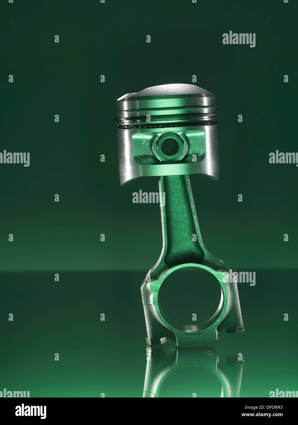 Car piston on green background - Stock Image