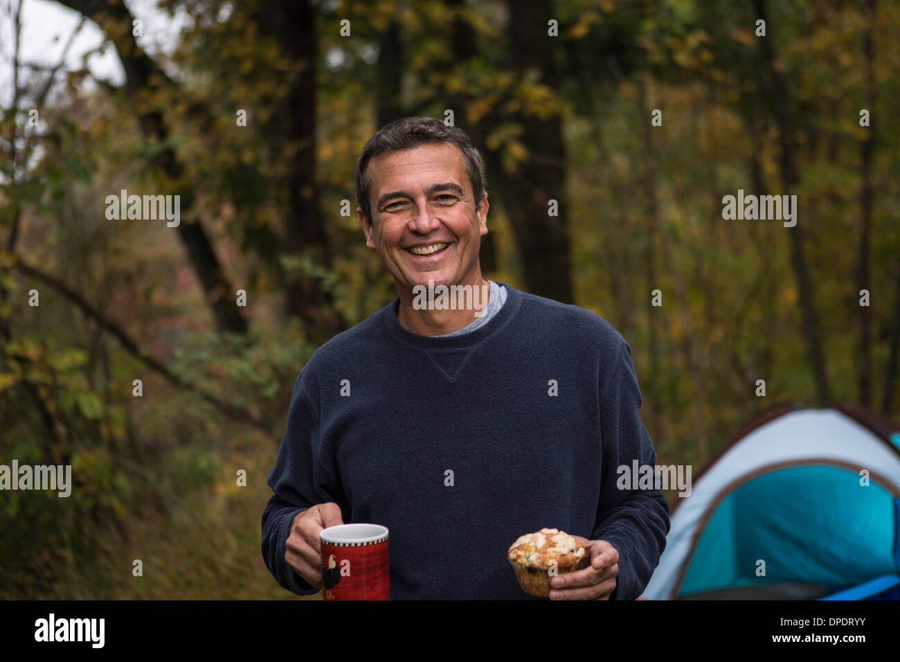 Mature man in forest holding cupcake and hot drink - Stock Image