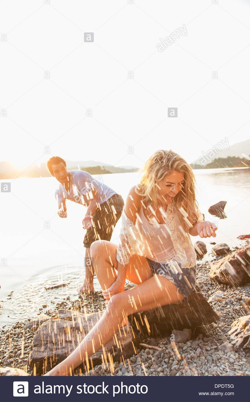 Young couple by lake, man splashing woman, Cumbria, England, UK - Stock Image