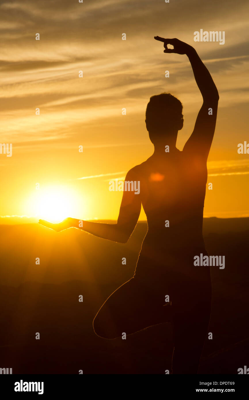 Young woman doing yoga in sunlight, Moab, Utah, USA - Stock Image