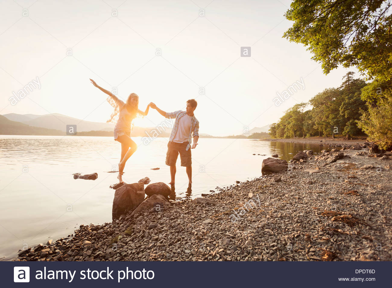 Young couple by lake, Cumbria, England, UK - Stock Image