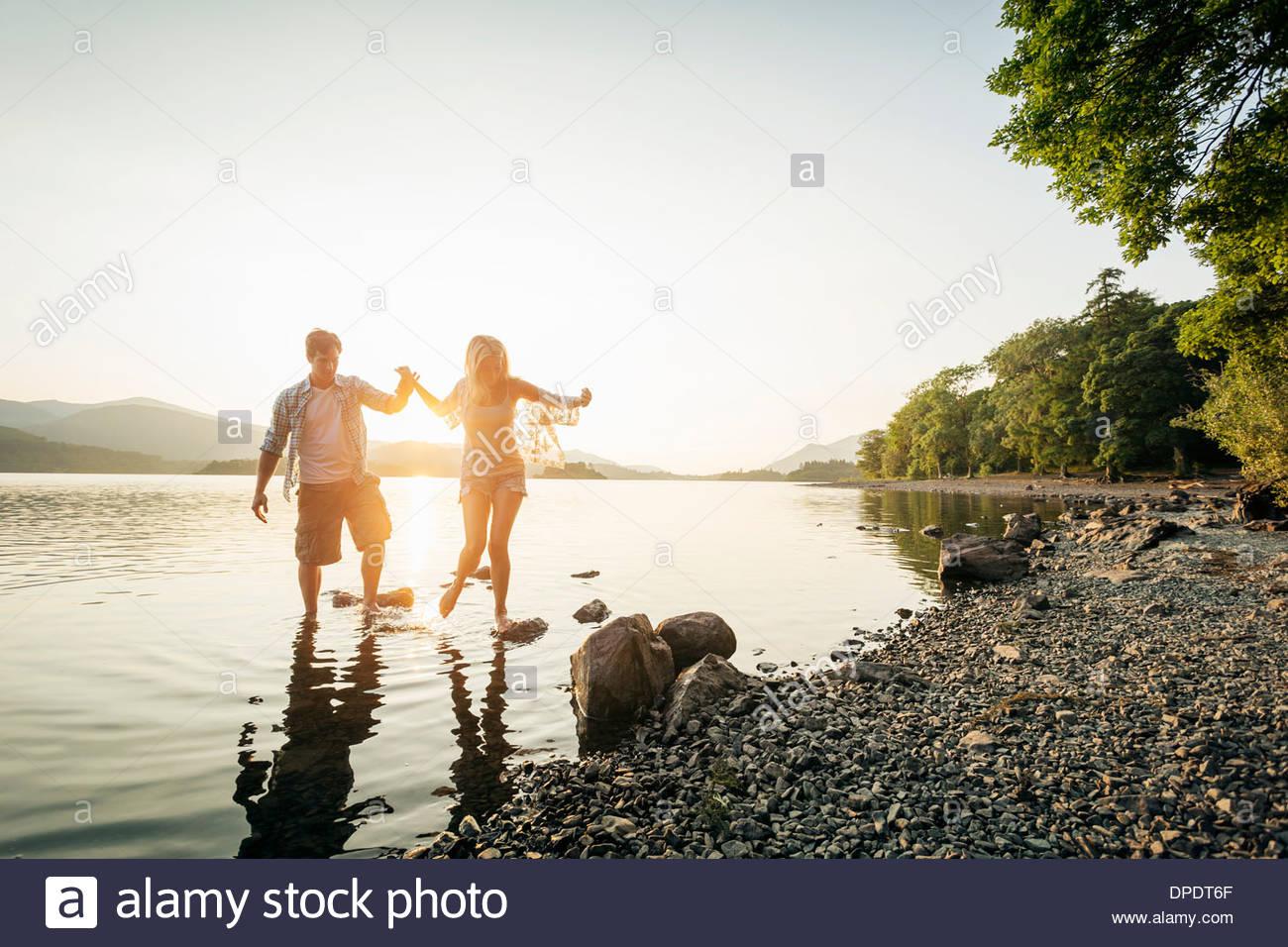Young couple paddling in lake, Cumbria, England, UK - Stock Image
