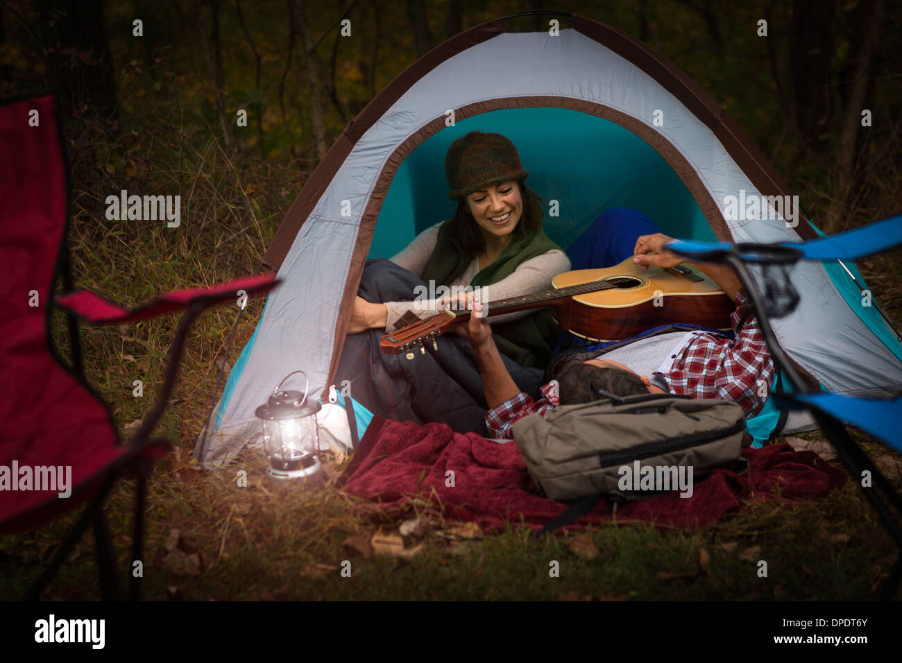 Mature couple sitting in tent, playing guitar - Stock Image
