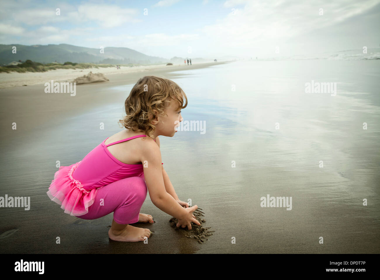 Portrait of female toddler playing in sand - Stock Image