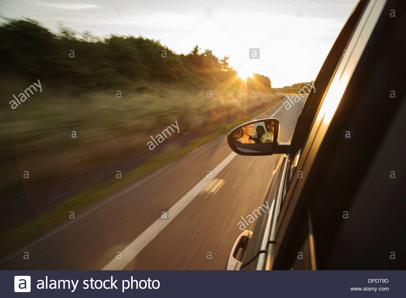 Car driving along road, reflection in wing mirror Stock Photo