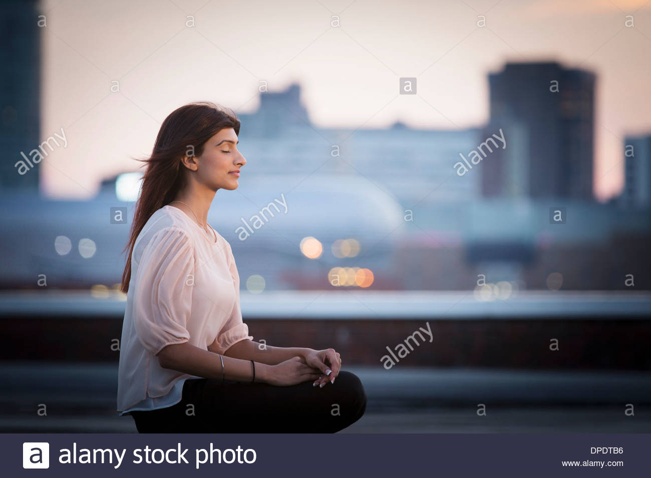 Woman meditating on rooftop - Stock Image
