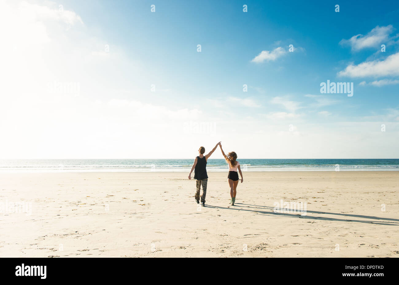 Young couple walking on San Diego beach, holding hands with arms raised Stock Photo