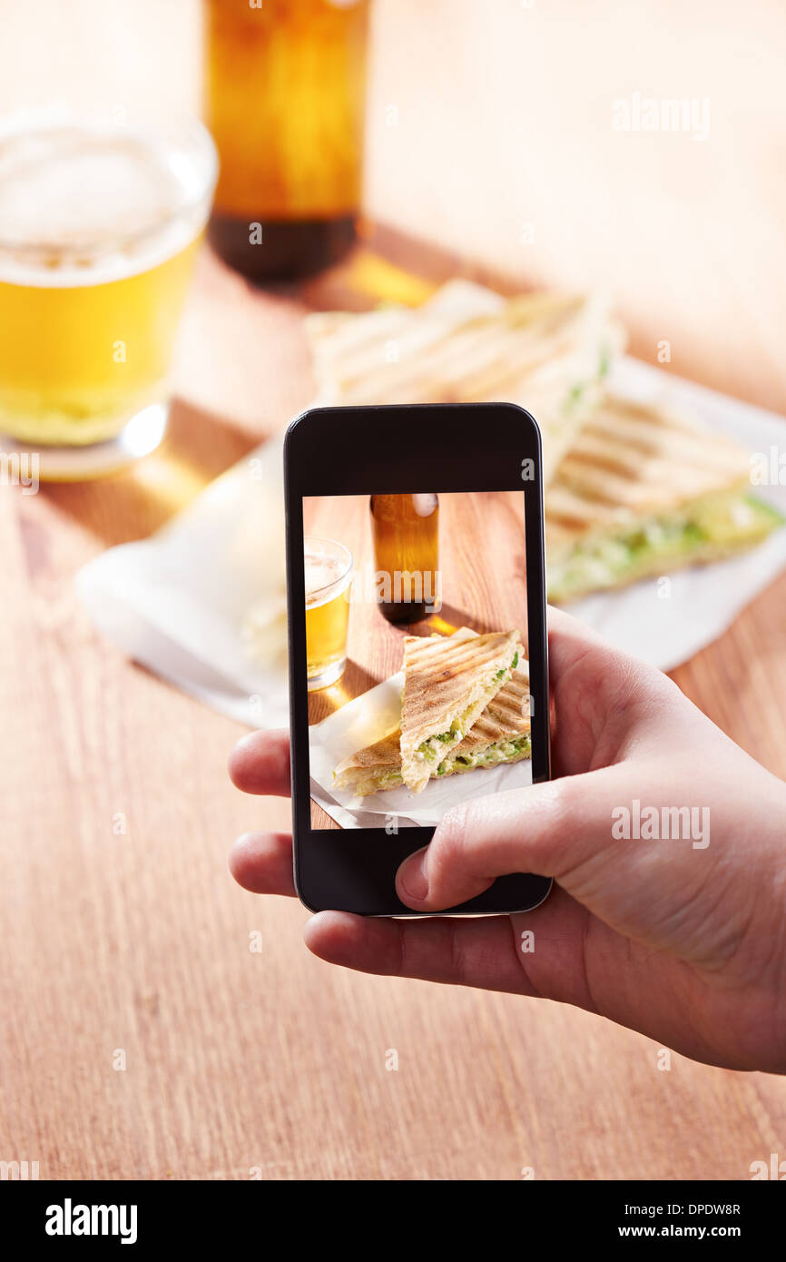 Smartphone taking photo of feta cheese sandwich on a restaurant - Stock Image