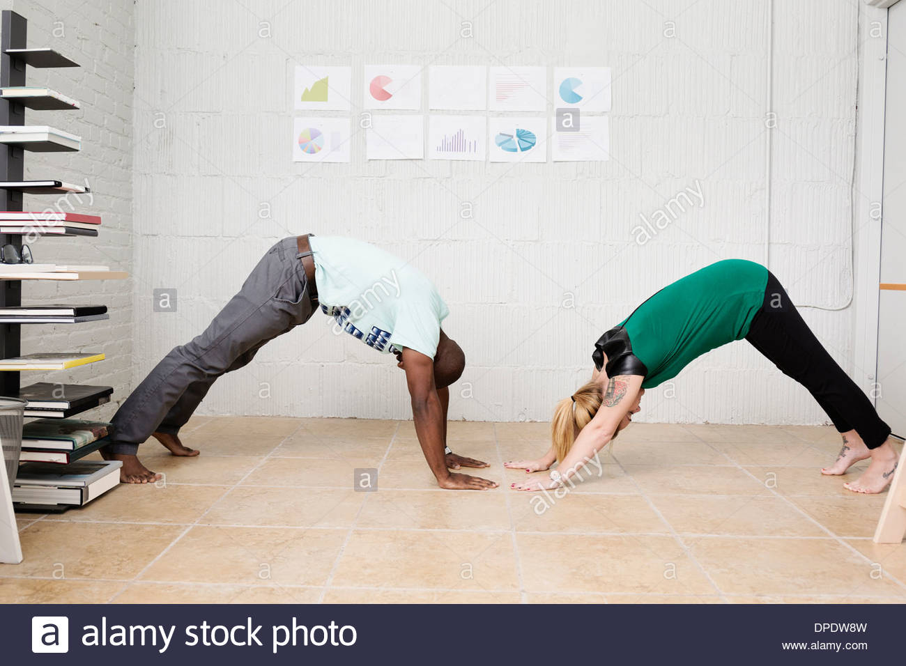 Young business partners exercising in design office - Stock Image
