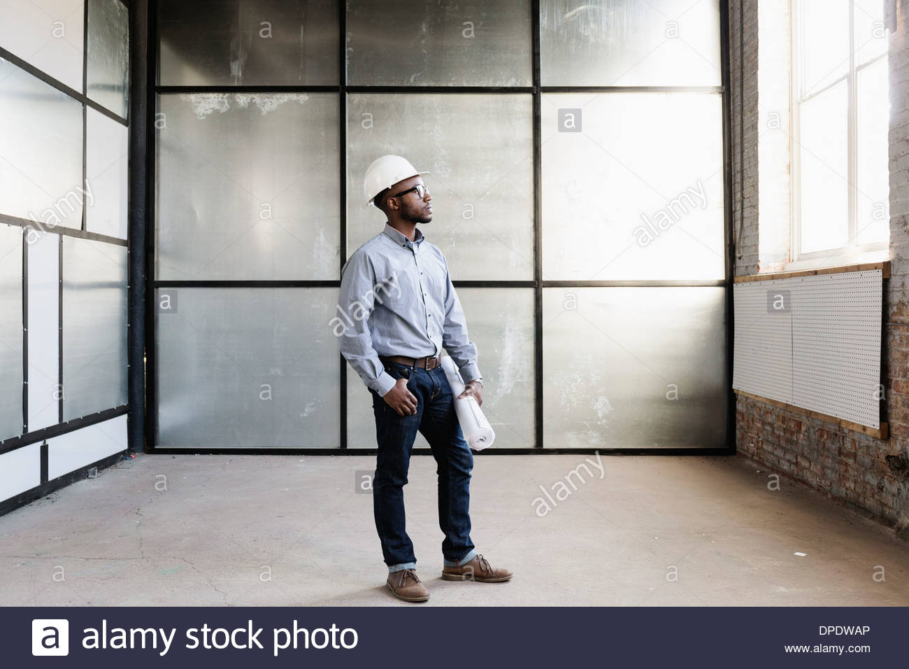 Portrait of young male interior designer in empty room - Stock Image