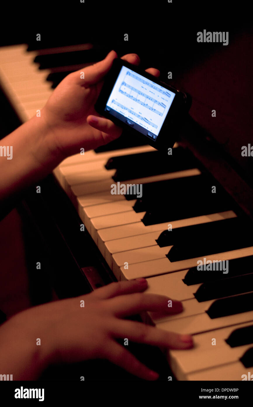 Close up of hands using smartphone whilst playing piano - Stock Image