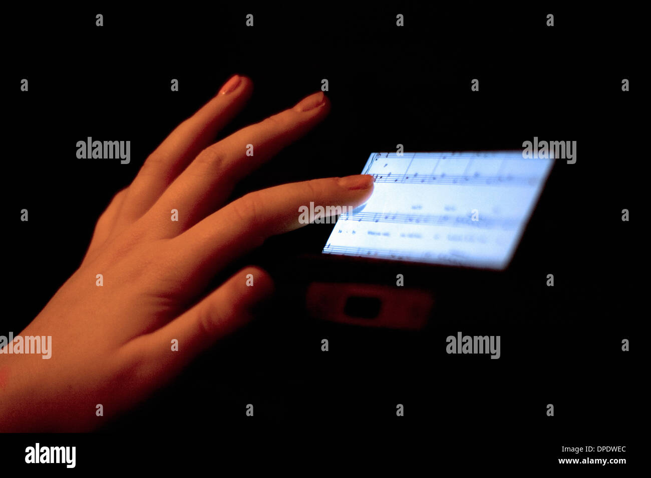 Close up of hand using touchscreen displaying sheet music - Stock Image