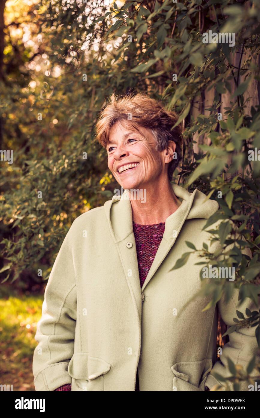 Portrait of mature woman in garden - Stock Image