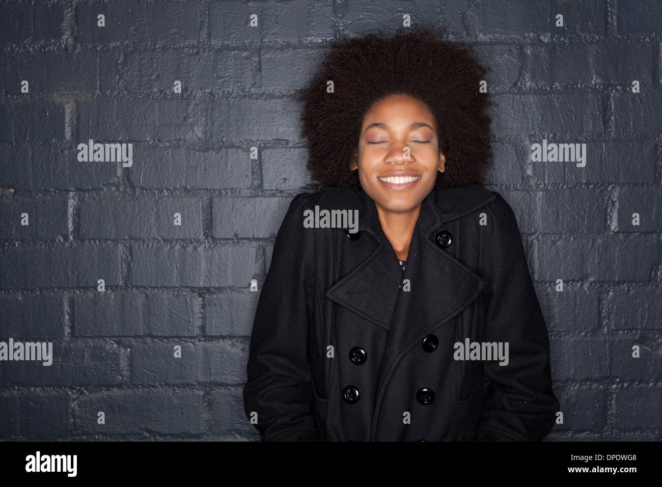Young woman by black brick wall wearing black jacket - Stock Image