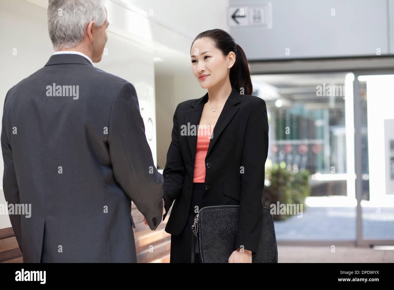 Businesspeople shaking hands - Stock Image