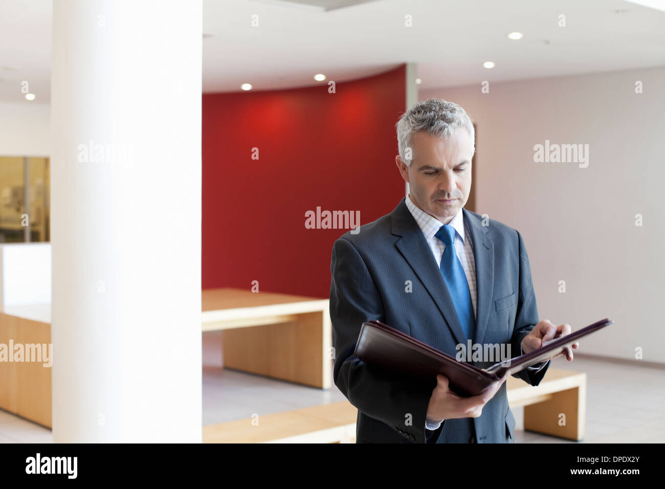 Businessman in waiting area of office, looking at paperwork - Stock Image